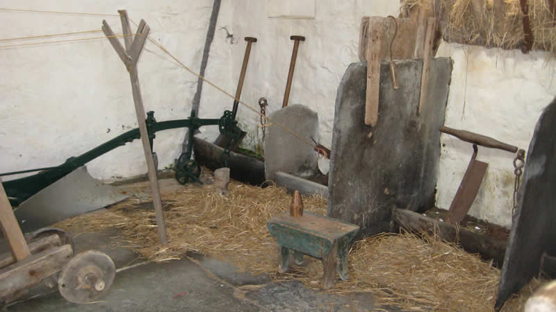 Inside barn - Collection of old farming equipment including ploughs and seeders