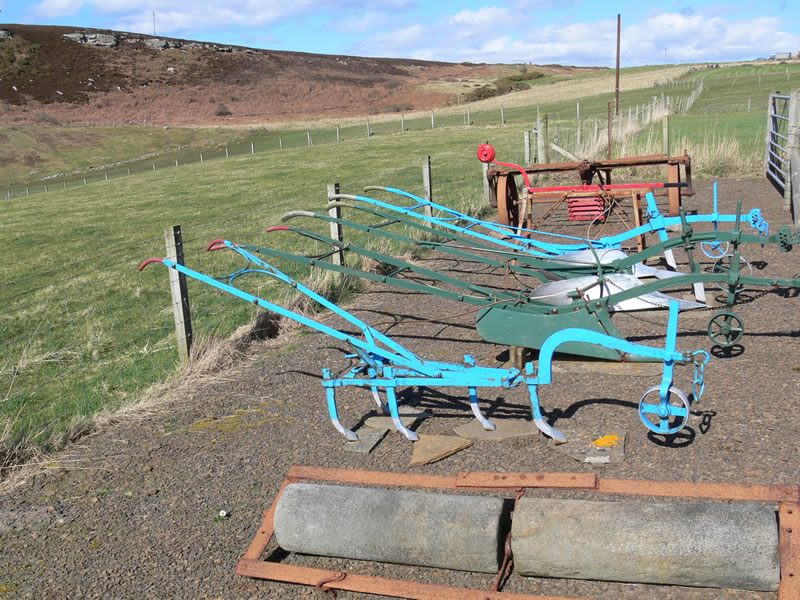 Collection of old farming equipment including ploughs and seeders